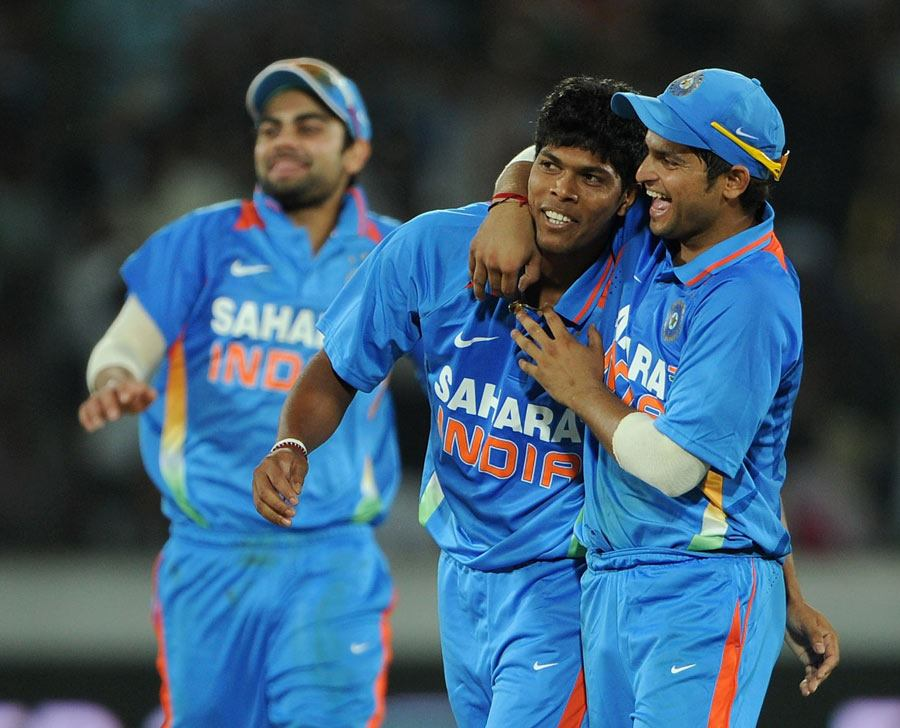 Umesh Yadav is congratulated by teammates after his first wicket in India